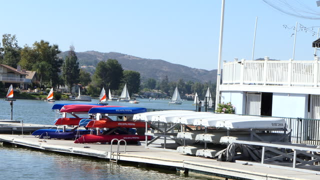zoom out from sailboats and watercraft on small lake to docks and racks of canoes westlake village a small southern california city in los angeles... - westlake village california stock videos & royalty-free footage
