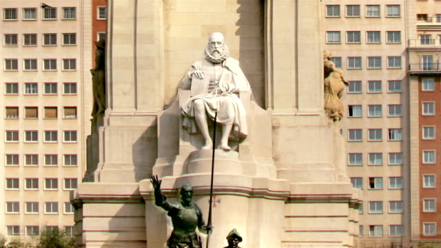 stockvideo's en b-roll-footage met zoom out from sculpture of spanish writer miguel de cervantes at plaza de espana to view across reflecting pool of visitors walking around base of monument in fast motion / madrid, spain - literature