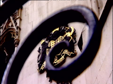 Zoom out from seal for Royal Courts of Justice seen through spiral feature on surrounding iron gate