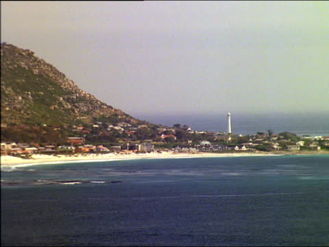 Zoom out from settlement on headland revealing sandy bay in foreground, South Africa