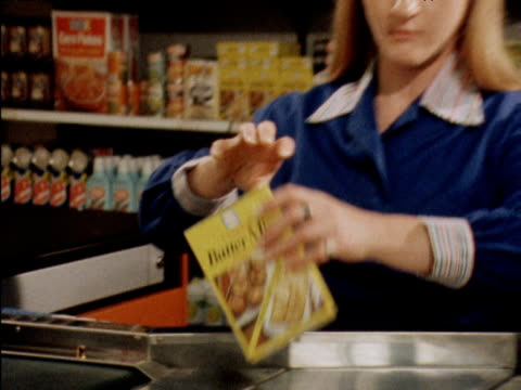 vídeos de stock e filmes b-roll de zoom out from shopping items to reveal check out girl scanning bar codes for customer introduction of bar codes; 25 july 79 - vendas