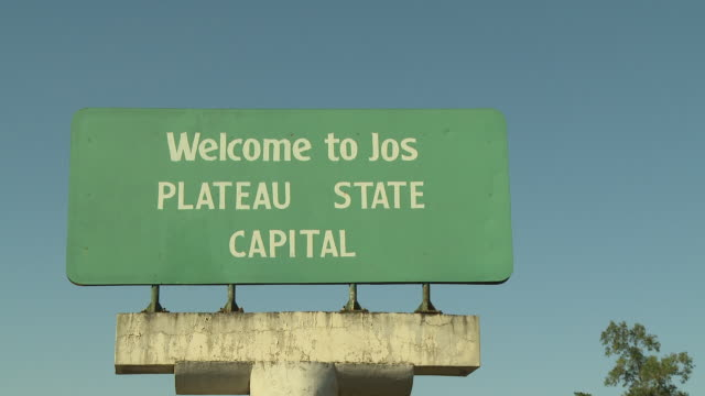 zoom out from sign on highway welcome to jos nigeria is home to nearly 200 million people which has earned it the name giant of africa it is an oil... - jos nigeria stock videos & royalty-free footage