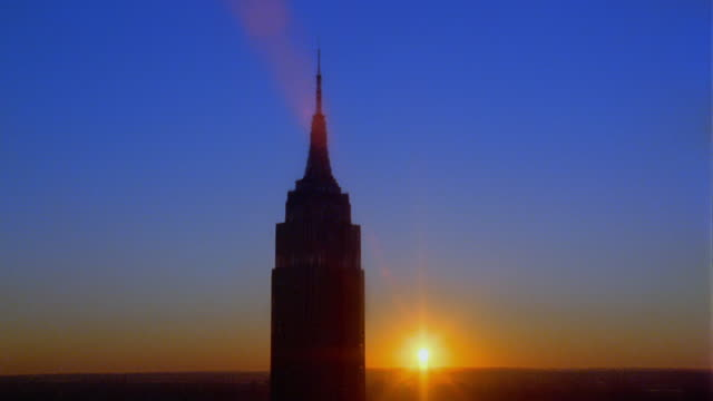 zoom out from silhouetted close up top of empire state building with sunset in background / manhattan, new york city - エンパイアステートビル点の映像素材/bロール