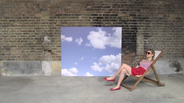 stockvideo's en b-roll-footage met zoom out from sky backdrop to show girl in deckchair - canvas