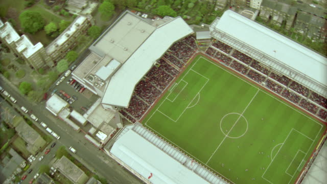 AERIAL zoom out from stands to soccer stadium during game / zoom in + zoom out from field / Arsenal FC, London