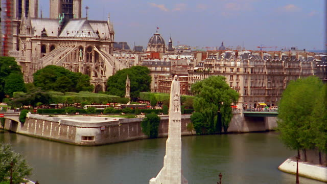 vidéos et rushes de zoom out from statue on pont de la tournelle to wide shot seine river with notre dame and buildings in background / paris - pont