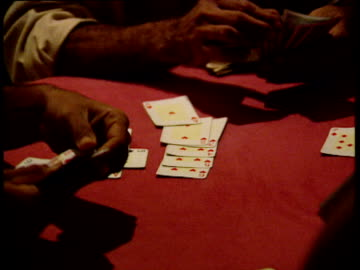 zoom out from table as men play cards in small dark room - poker stock-videos und b-roll-filmmaterial