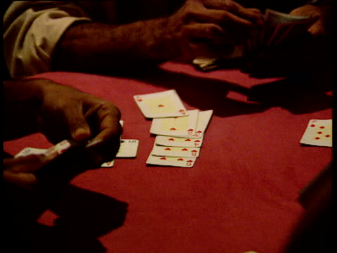 vídeos de stock, filmes e b-roll de zoom out from table as men play cards in small dark room - pôquer