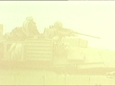 zoom out from tank with soldiers to reveal tanks in line in sand storm during iraq war 25 mar 03 - 軍用輸送車点の映像素材/bロール