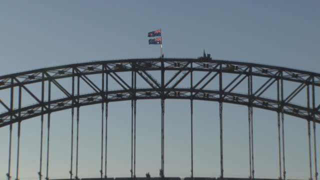 Zoom out from the Australian flag to a long shot of the Sydney Harbour Bridge.