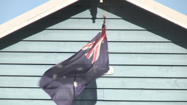 Zoom out from the Australian national flag to a beach house at the end of a pier.