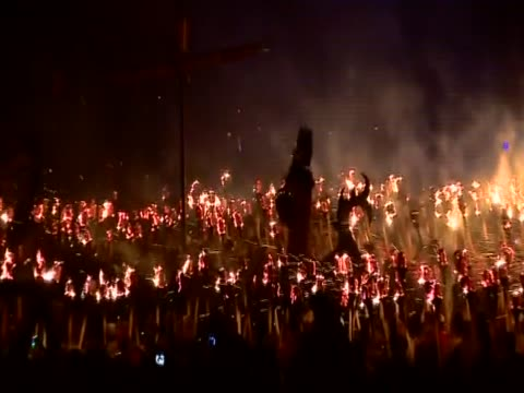 stockvideo's en b-roll-footage met zoom out from the jarl standing on a replica viking galley surrounded by the jarl squad holding flaming torches for the up helly aa festival - omgeven