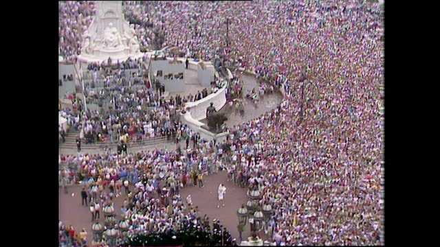 zoom out from the large crowd waiting outside buckingham palace as it erupts with a massive cheer on the day of the wedding of prince charles and... - fountain stock videos & royalty-free footage