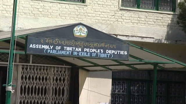 zoom out from the parliament inexile of tibet sign to a tibetan woman crossing the courtyard the first elections took place in 1960 - rock face stock videos & royalty-free footage