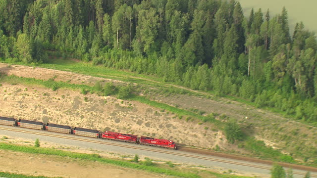 Zoom out from train running parallel to the Columbia River to surrounding wilderness. Available in HD.