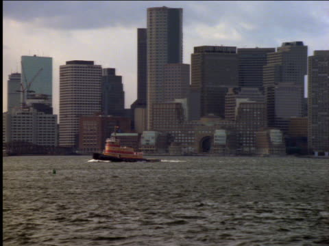 zoom out from tugboat on river to boston skyline in background - boston massachusetts stock videos & royalty-free footage