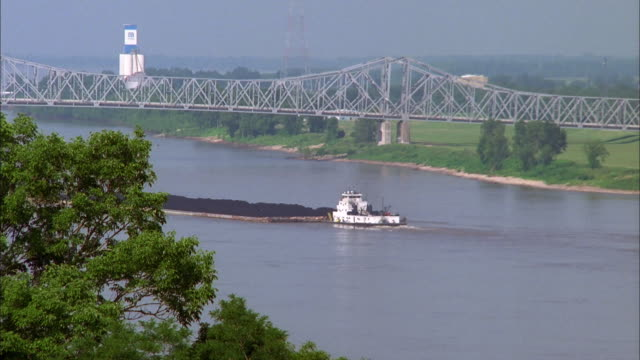zoom out from tugboat pushing load towards bridge on mississippi river, natchez available in hd. - north stock videos & royalty-free footage