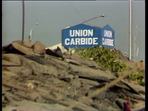 Zoom out from Union Carbide sign to families living in slums below factory Bhopal Dec 84