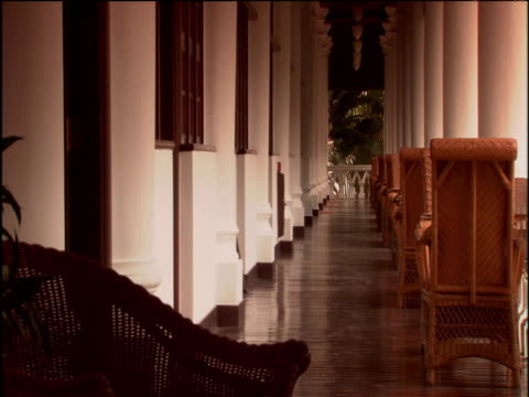 zoom out from verandah with row of wicker chairs raffles hotel singapore - 2000年風格 個影片檔及 b 捲影像