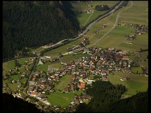 zoom out from village in valley to reveal surrounding forested hills and mountains mayrhofen - tyrol state austria stock videos and b-roll footage