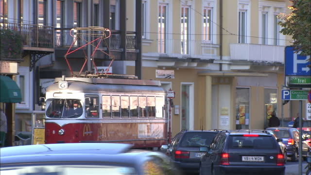 stockvideo's en b-roll-footage met zoom out from vintage red tram pulling away from stop in busy street - trambaan