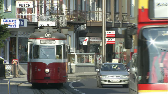 vídeos de stock e filmes b-roll de zoom out from vintage red tram running alongside traffic on busy street - linha do elétrico