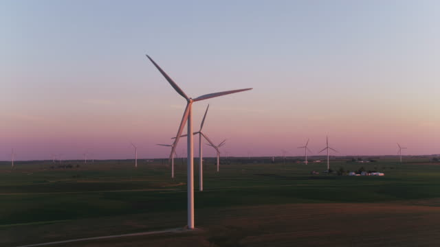 Zoom out from wind farm at sunset