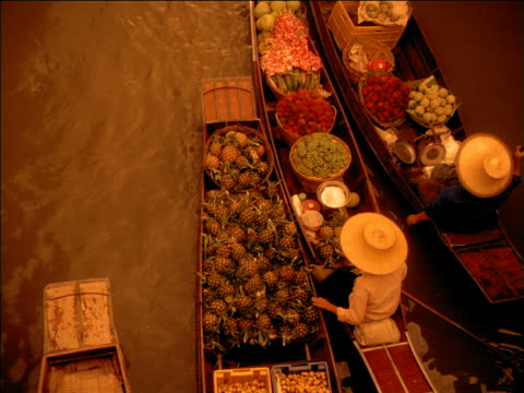 zoom out from woman buying pineapples in floating food market as other boats pass by, bangkok - bangkok stock videos & royalty-free footage