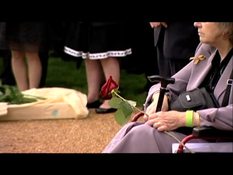 zoom out from woman holding single red rose during service in honour of 7/7 bombing victims at new memorial garden london 7 july 2009 - single rose stock videos & royalty-free footage