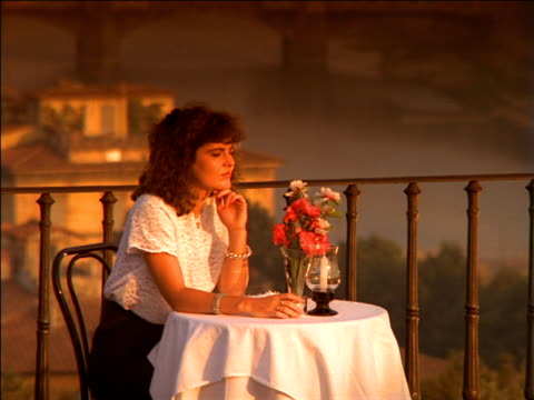 Zoom out from woman sitting at table of roof terrace restaurant at sunset with Ponte Vecchio Bridge in distance, Florence