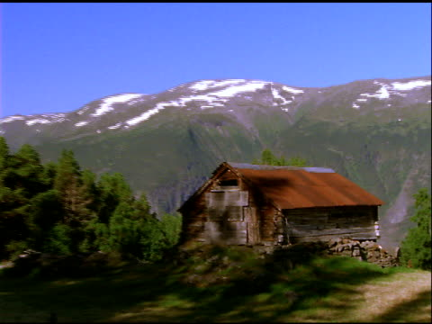 zoom out from wood cabin with rusty corrugated iron roof, mountains in background, norway - imperfection stock videos & royalty-free footage