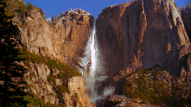 Zoom out from Yosemite Falls on rock to reveal lake/river below in Winter / Yosemite National Park, California