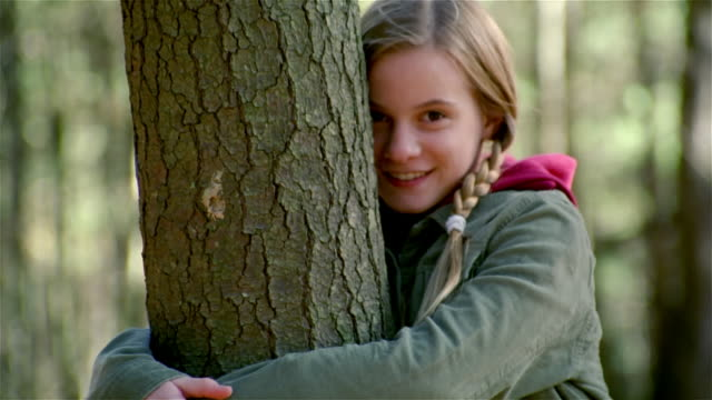 zoom out girl hugging tree in woods and smiling at camera - tree hugging stock videos & royalty-free footage