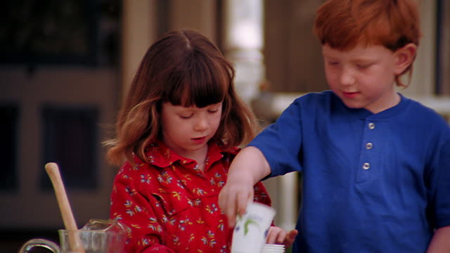 ms zoom out girl + redheaded boy setting up cups at lemonade stand in front of house - traditional lemonade stock videos & royalty-free footage