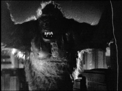 stockvideo's en b-roll-footage met b/w zoom out gorilla (costume) standing amongst city buildings (miniature) growling - 1933