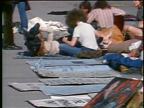 stockvideo's en b-roll-footage met 1972 zoom out hippies lying sitting on ground holding posters on washington dc street / peace sign - vredesteken handgebaar