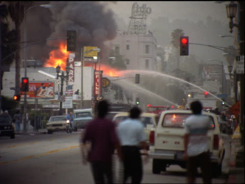 vídeos de stock e filmes b-roll de zoom out hoses spraying burning building / traffic + people on street foreground / los angeles riots - 1992