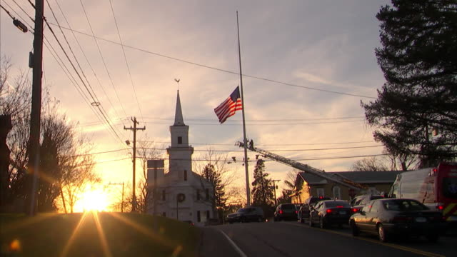 zoom out if firefighters lowering flag in newtown ct at dusk - herunterlassen stock-videos und b-roll-filmmaterial