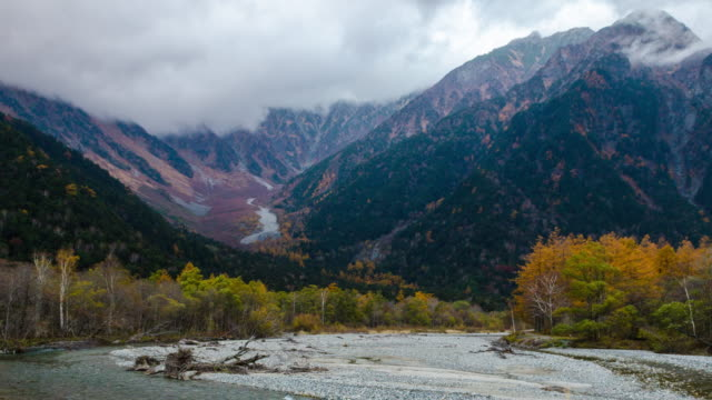 4k zoom out kamikochi national park landscape view with river and leaves color change in nagano prefecture, japan - nagano prefecture stock videos & royalty-free footage
