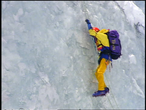 zoom out male climber with backpack climbing icy mountainside on rope ladder / Mt Everest expedition