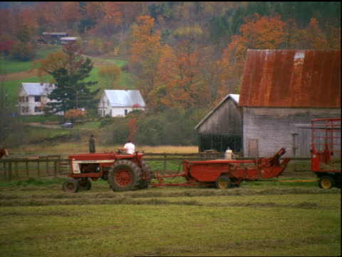 zoom out pan of man driving tractor with hay baler in field in autumn / farm buildings in background / vermont - hay baler stock videos & royalty-free footage