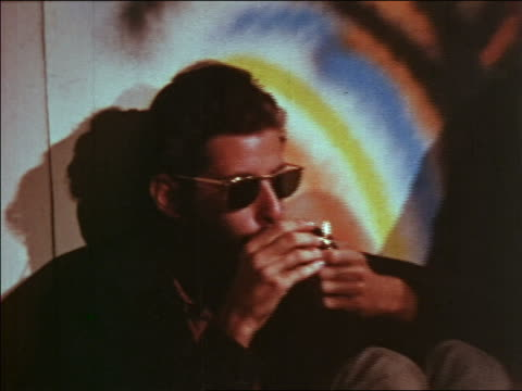 1969 zoom out man in sunglasses lighting marijuana pipe next to second man at party / educational