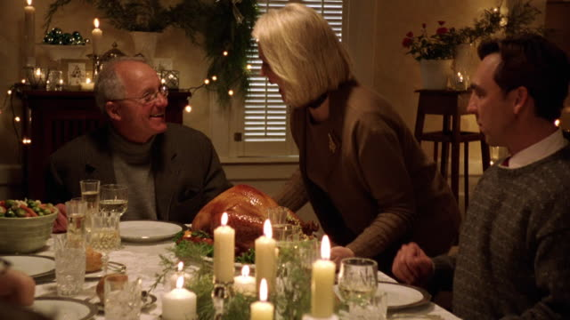 zoom out mature woman bringing turkey to christmas dinner table with family and hugging husband - large family stock videos & royalty-free footage