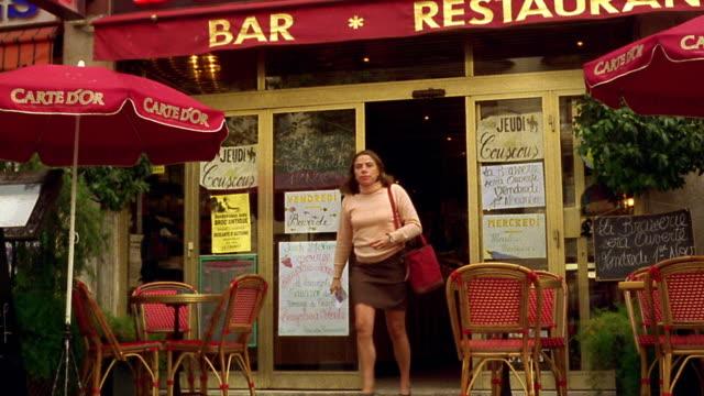 vídeos de stock, filmes e b-roll de zoom out medium shot pan woman exiting restaurant with outdoor seating / cannes, france - vão de porta