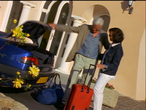 zoom out middle-aged couple putting luggage into trunk of car then kissing in front of house / Corsica