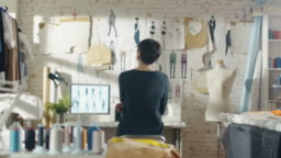 Zoom Out of a Female Fashion Designer Looking at Drawings and Sketches that are Pinned to the Wall Behind Her Desk. Studio is Sunny. Personal Computer, Colourful Fabrics, Sewing Items are Visible.