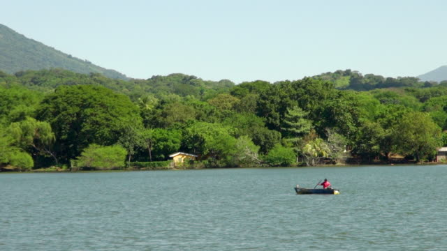 zoom out of a man boating on the wavy ocean - nicaragua stock videos and b-roll footage