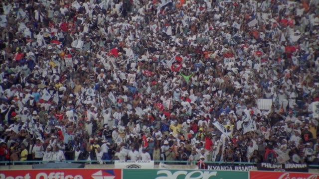 Zoom out of a stadium stand packed with excited soccer spectators
