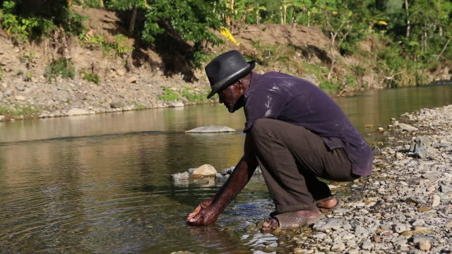 a zoom out of an elderly man who is sitting in a squat at a river while he is washing his face in pilate haiti - afro caribbean ethnicity stock videos and b-roll footage