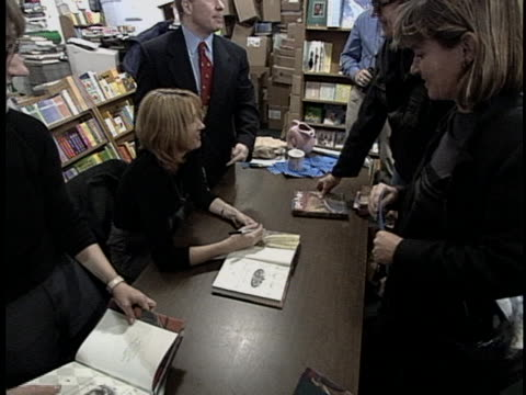 zoom out of author j.k. rowling signing copies of books from the harry potter series. the harry potter book series was started by rowling while she... - author stock videos & royalty-free footage